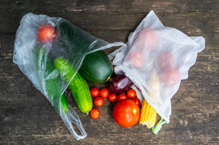 Produce in single use plastic bags and plastic free reusable shopping bags on a wooden surface in nature. Zero waste lifestyle.