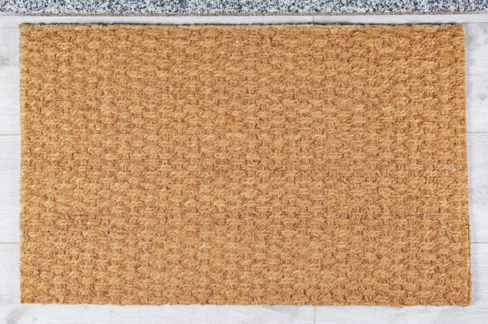 Door mat near stone stairs indoors, top view. Space for design