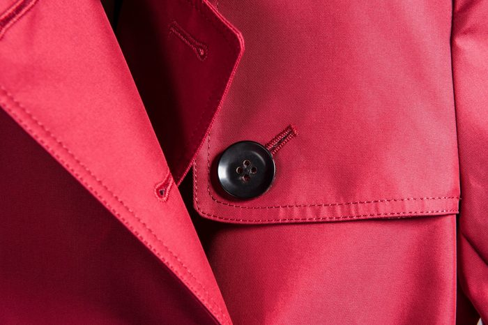 Partial close-up of neckline of red trench coat