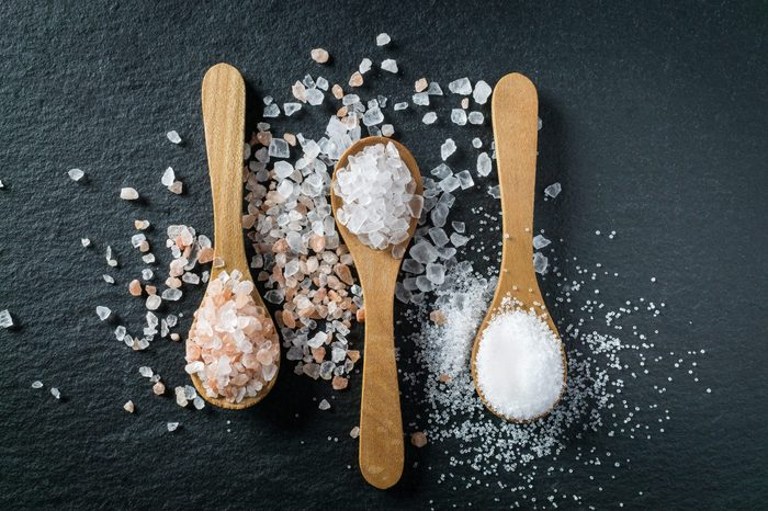 Different types of salt. Sea, himalayan and kitchen salt. Top view on three wooden spoons on black background