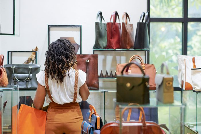 Pensive stylish young woman looking at various leather bags on shelves in department store