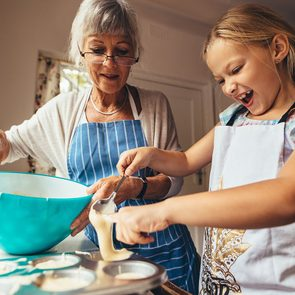 Little girl learning to make cup cakes with her grandmother. Excited girl pouring cake batter in cup cake moulds.; Shutterstock ID 1476944876; Job (TFH, TOH, RD, BNB, CWM, CM): TOH