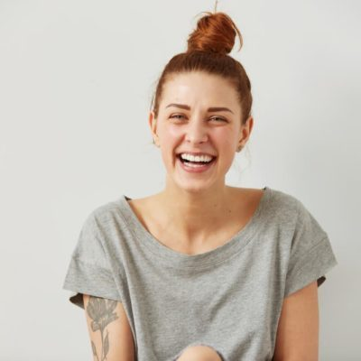 Happy woman Laughing. Closeup portrait woman smiling with perfect smile and white teeth looking laugh loudly isolated grey wall background. Positive human emotion facial expression body language.