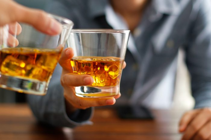 Close-up of two men clink glasses of whiskey drink alcoholic beverage together while at bar counter in the pub