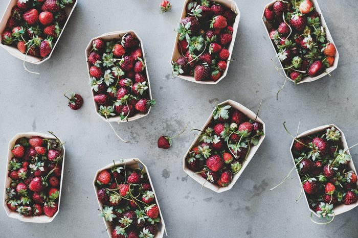 Fresh seasonal summer local market fruit produce. Flat-lay of garden harvest strawberries in eco-friendly plastic-free boxes over grey concrete background, top view