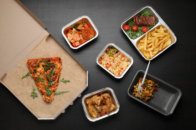 Different containers with delicious food on wooden table. Delivery service