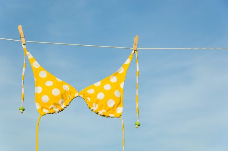 An itsy-bitsy teeny weeny yellow polka dot bikini hanging on a clothesline with copy space