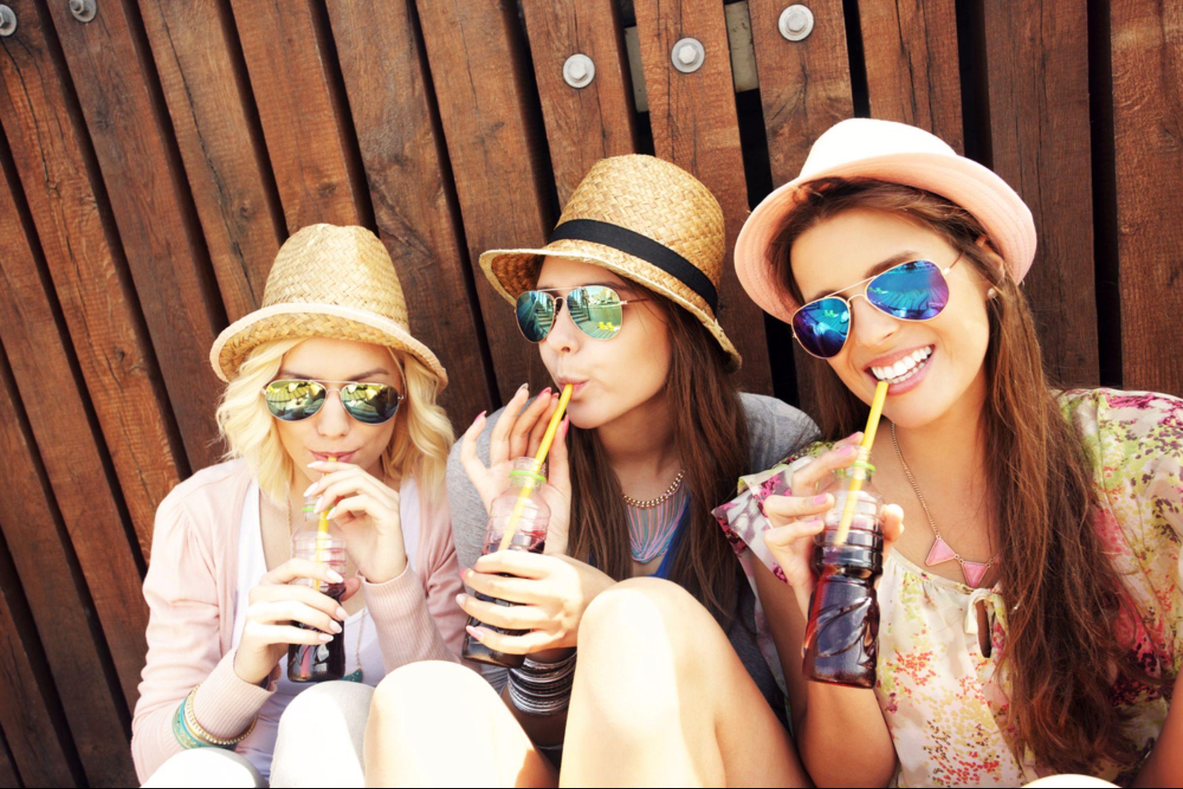 Three female friends drinking beverages