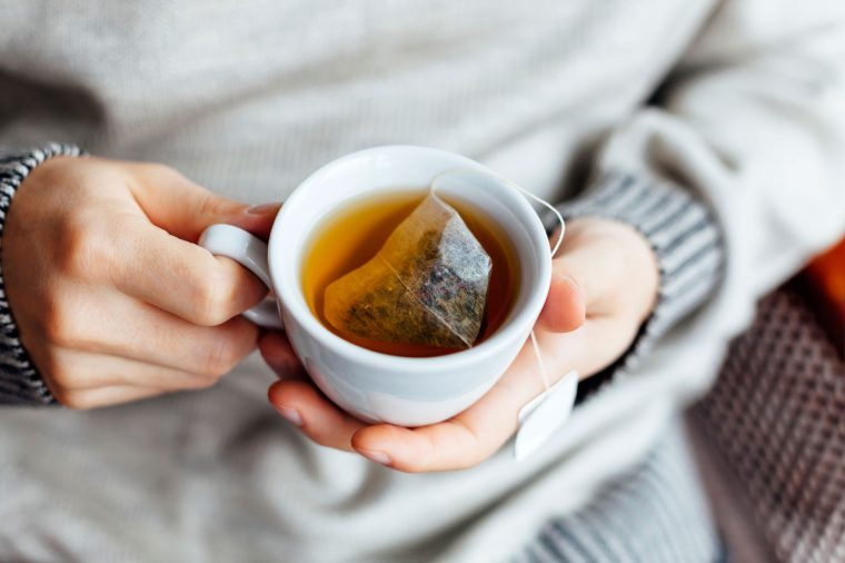 Person in a gray sweater holding a cup of tea