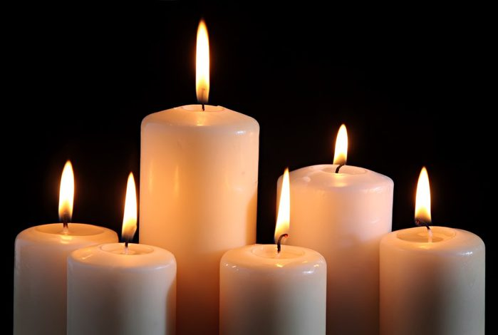 six candles on a black background.
