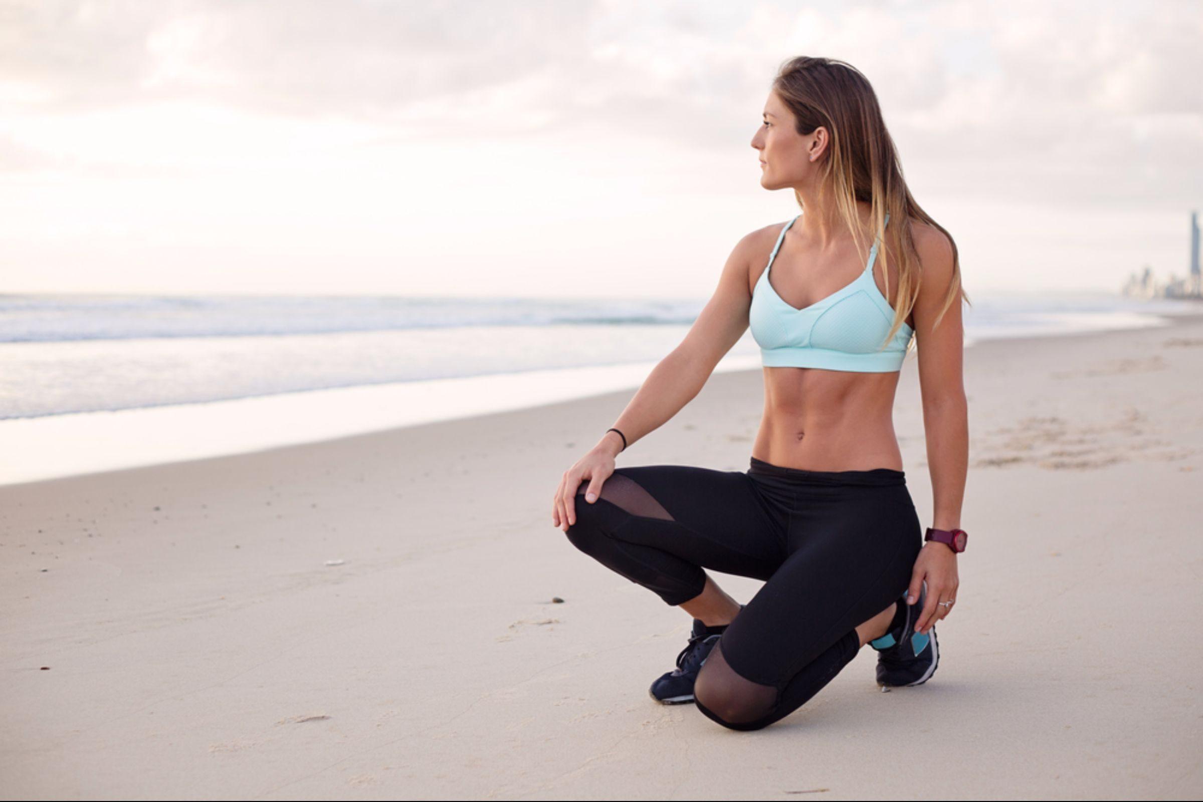 Female athlete posing on beachfront