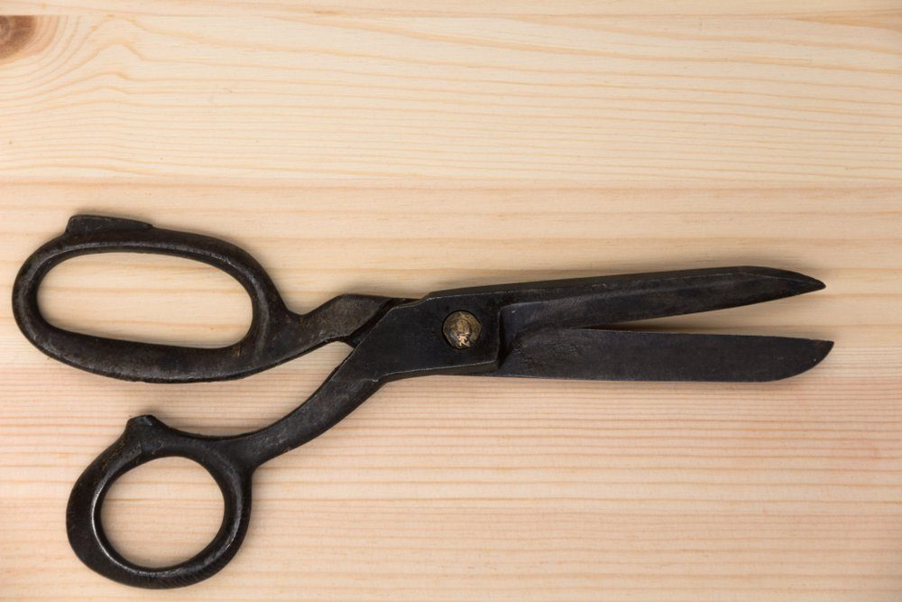 old tailor's scissors on a light wooden table