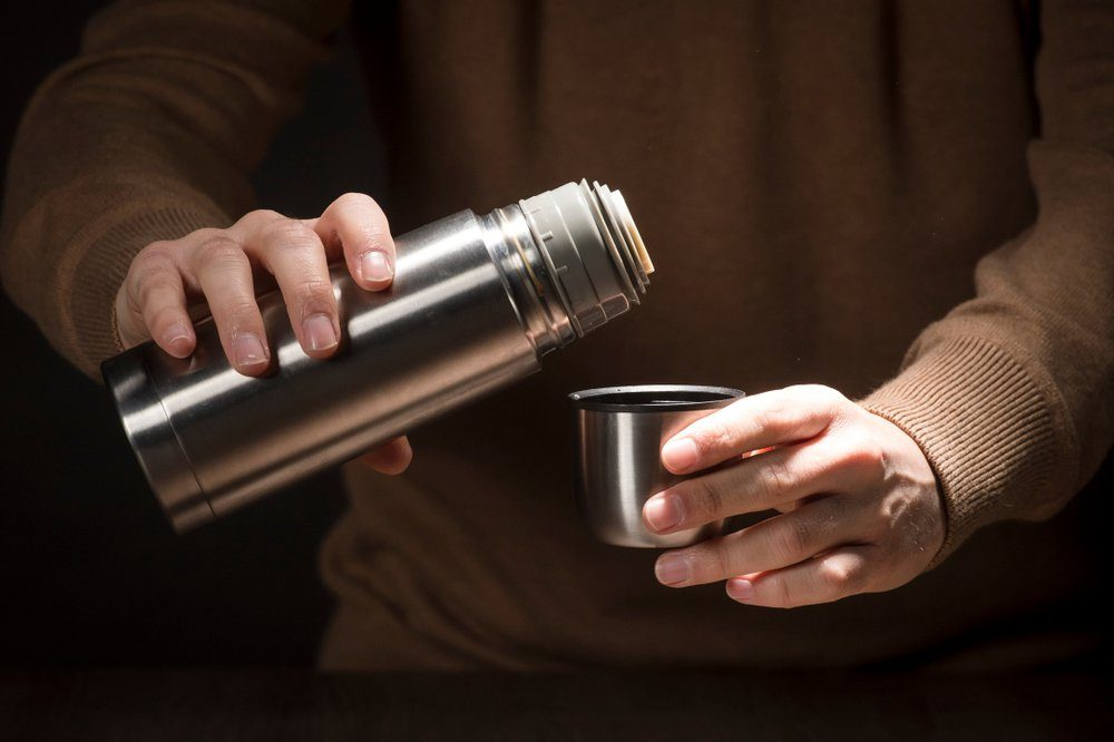 Metal thermos for trips in hand isolated on black background