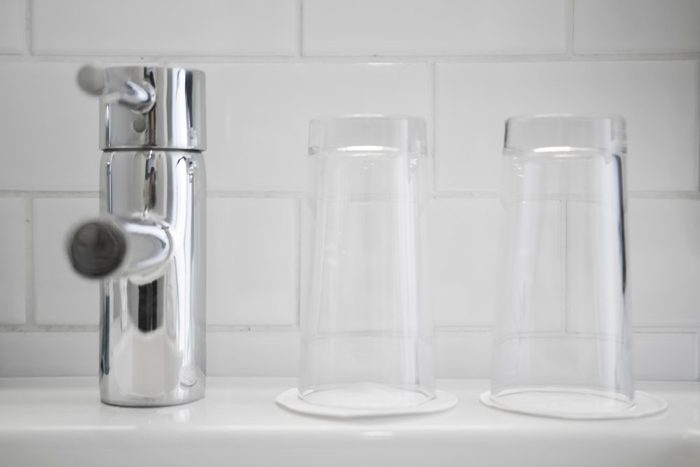 Mixer tap and two clean water glasses in the white bathroom.