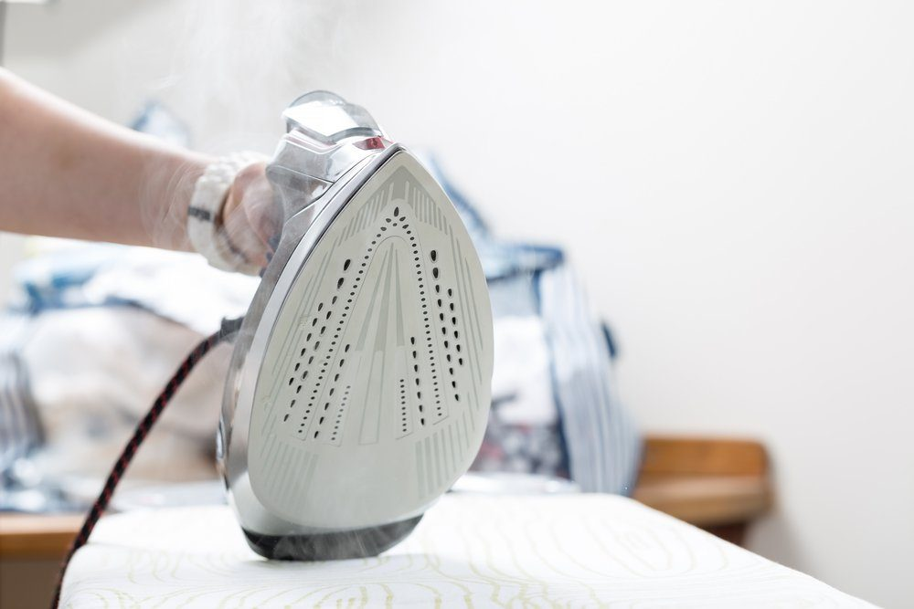 Woman uses irons, ironing at home.
