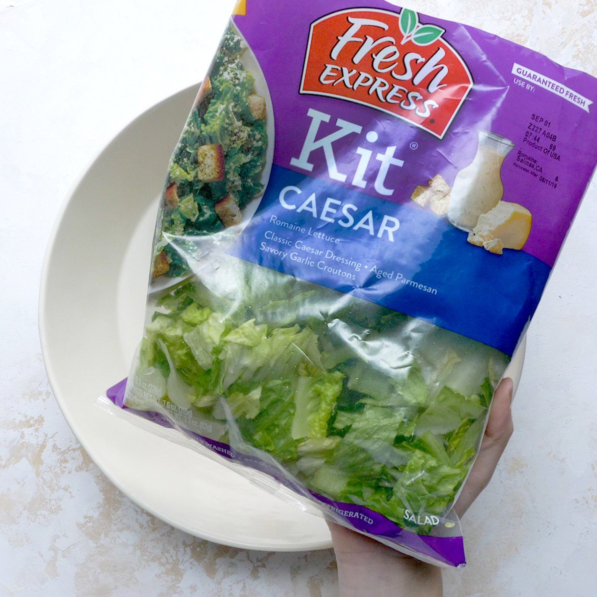 Salad kit over empty bowl