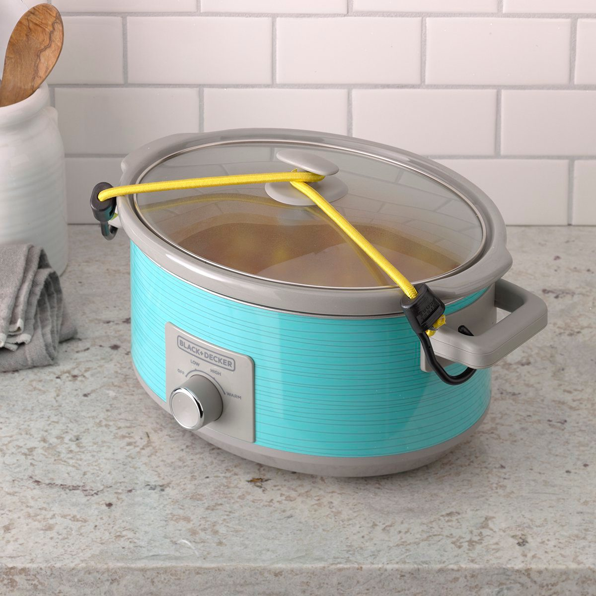 Slow cooker with bungee cord tied on for safe traveling.