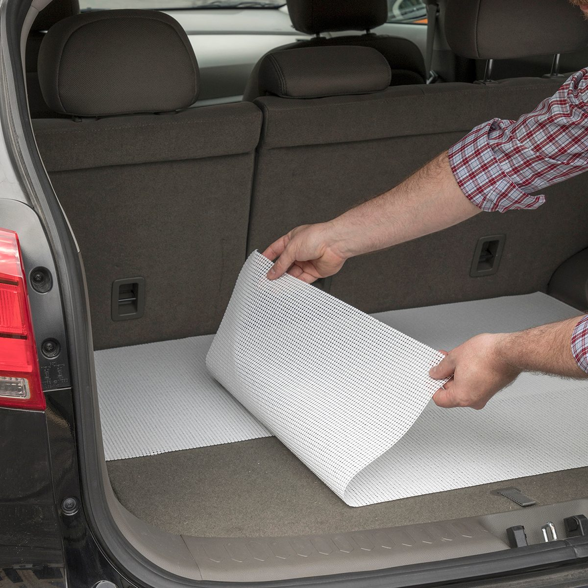 Man lining the trunk of a car with shelf liners