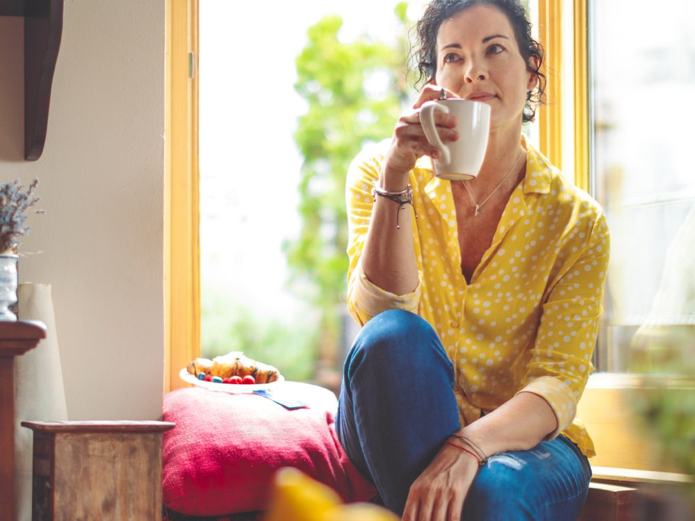 Woman enjoying a cup of coffee at home