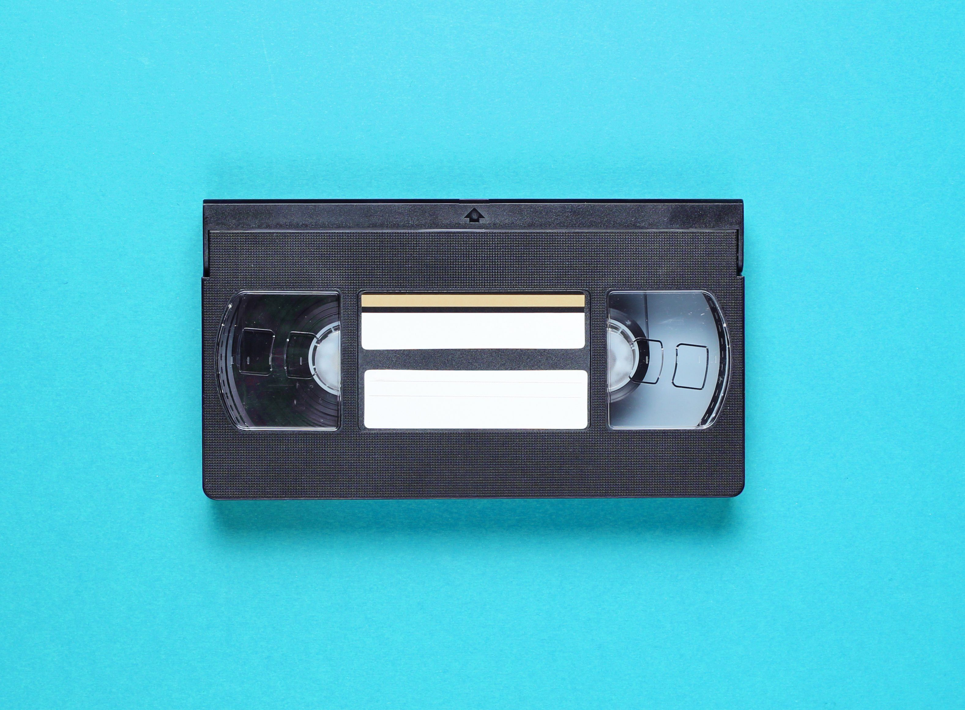 Pop culture retro attributes 80s, video cassette on blue background. Top view