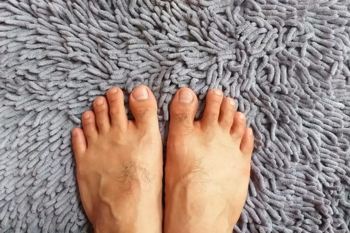Barefoot on carpet. Two feet standing. Gray carpet. Fluffy carpet. Top view.