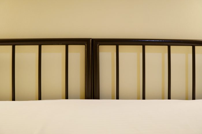 metal bed in a hotel room without pillows