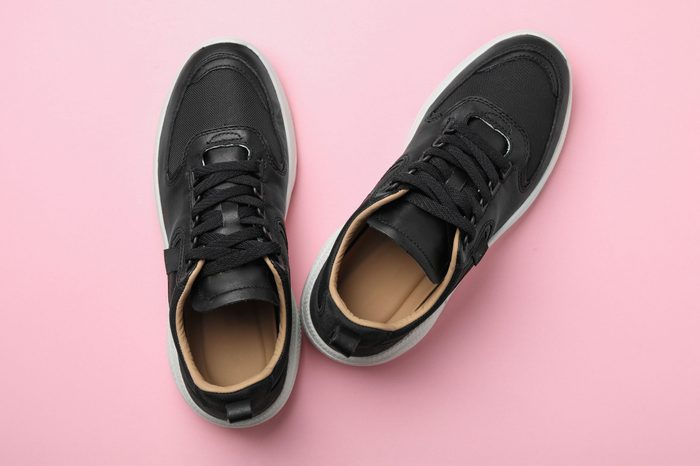 Pair of stylish shoes on pink background, top view