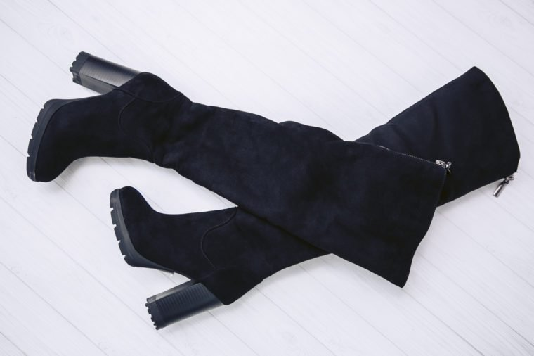 Luxury winter boots with high heels made from genuine black suede leather on a white wooden background