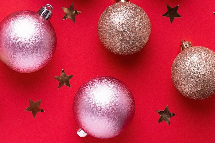 Creative Christmas card with golden balls and wrapped present on red background, copy space, minimalistic lay out