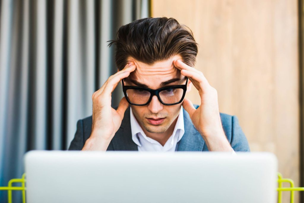 Man with glasses staring at computer screen