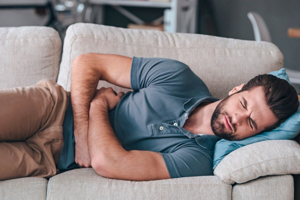 Man clutching stomach while lying on a couch