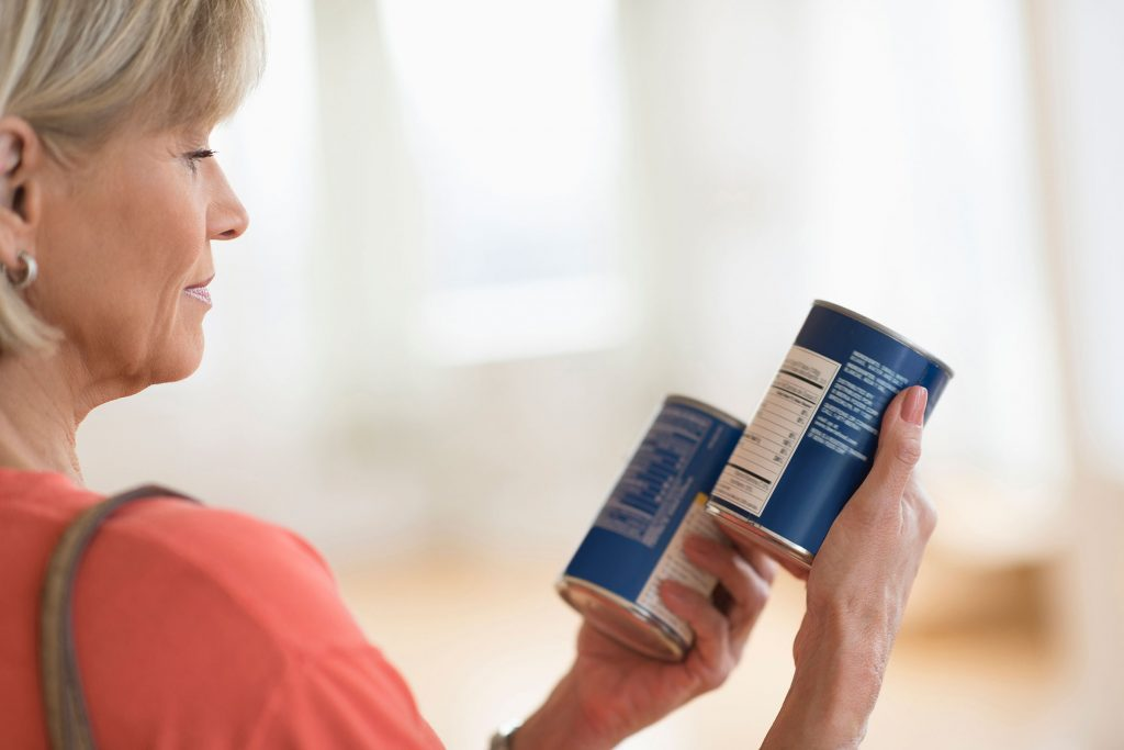 Woman comparing canned food products