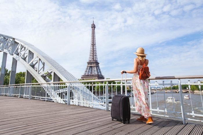 travel to Paris, Europe tour, woman with suitcase near Eiffel Tower, France