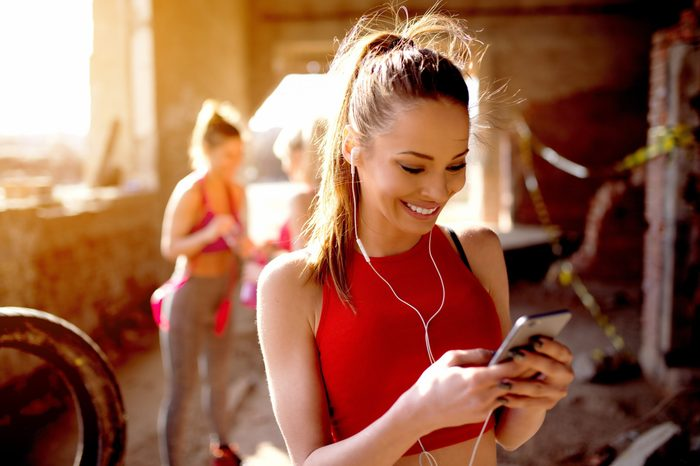 Beautiful young woman listening music fitness training workout. Group of fitness people behind preparing for training.