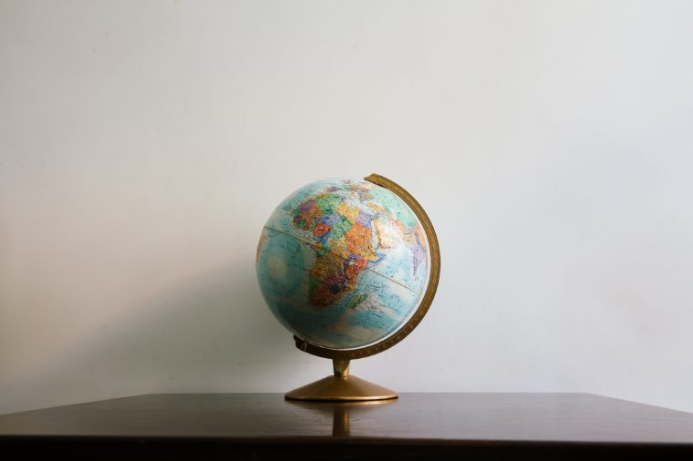 Globe model on dark wooden desk. White wall empty space background.