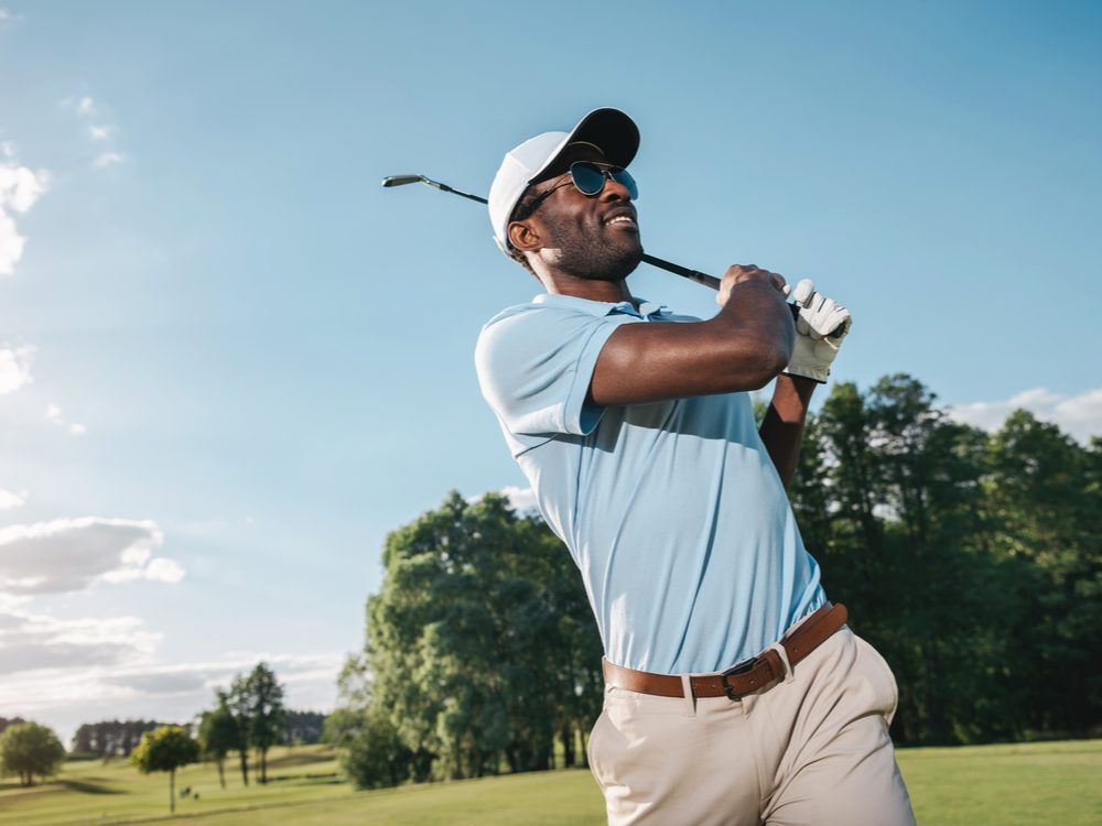 Man holding golf club over shoulder and smiling