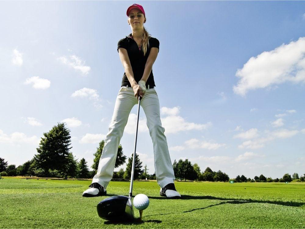 Woman putting golf ball