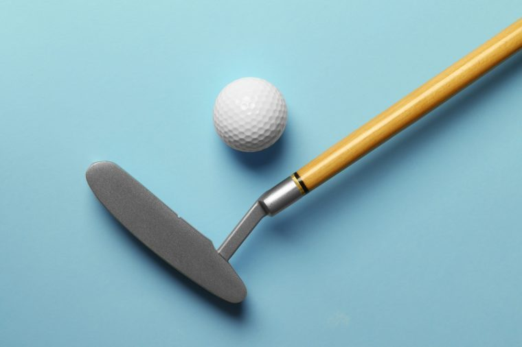 Golf ball and club on light blue background, flat lay. Space for text