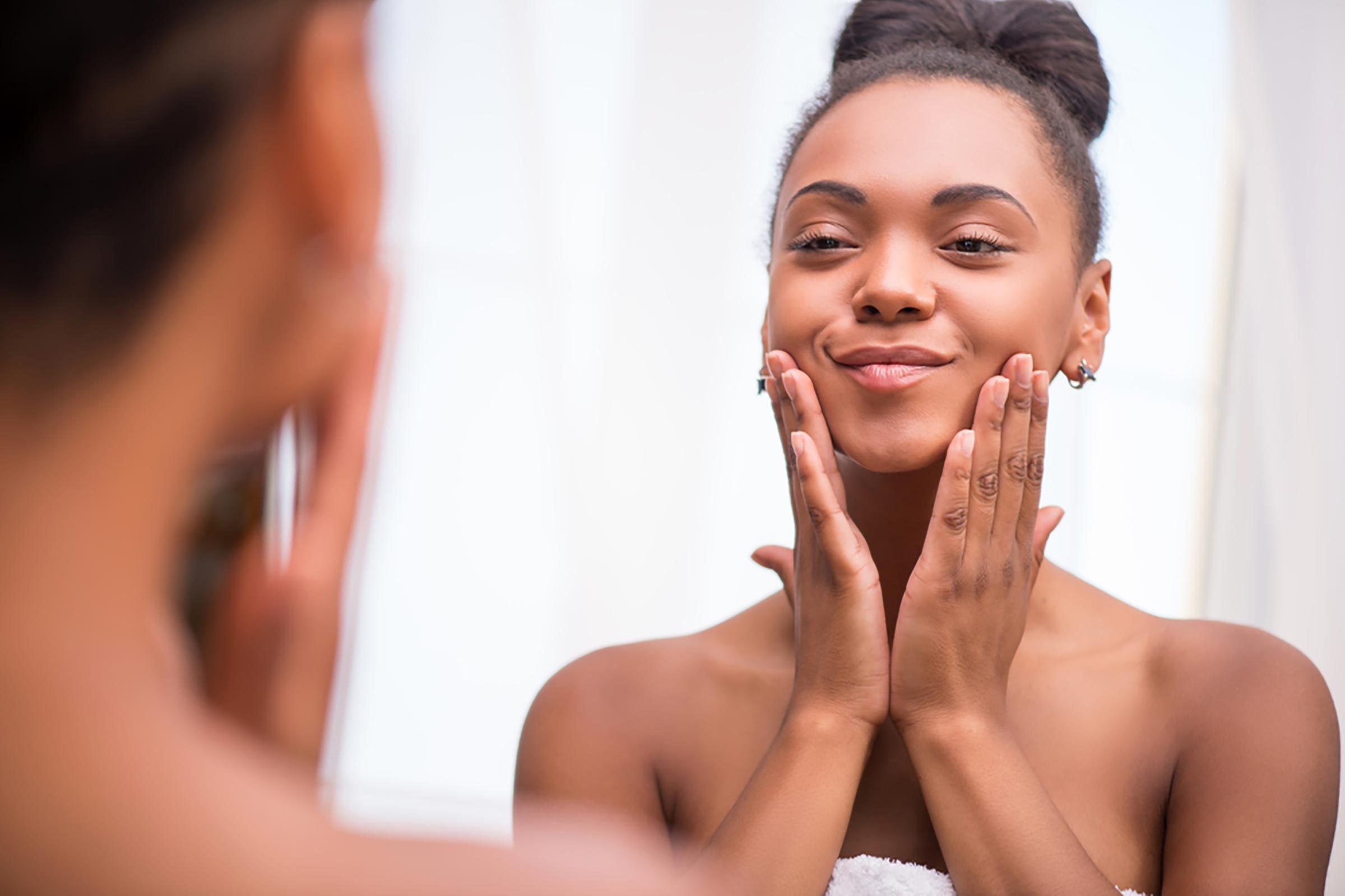 Woman smiling and examining her complexion in the mirror
