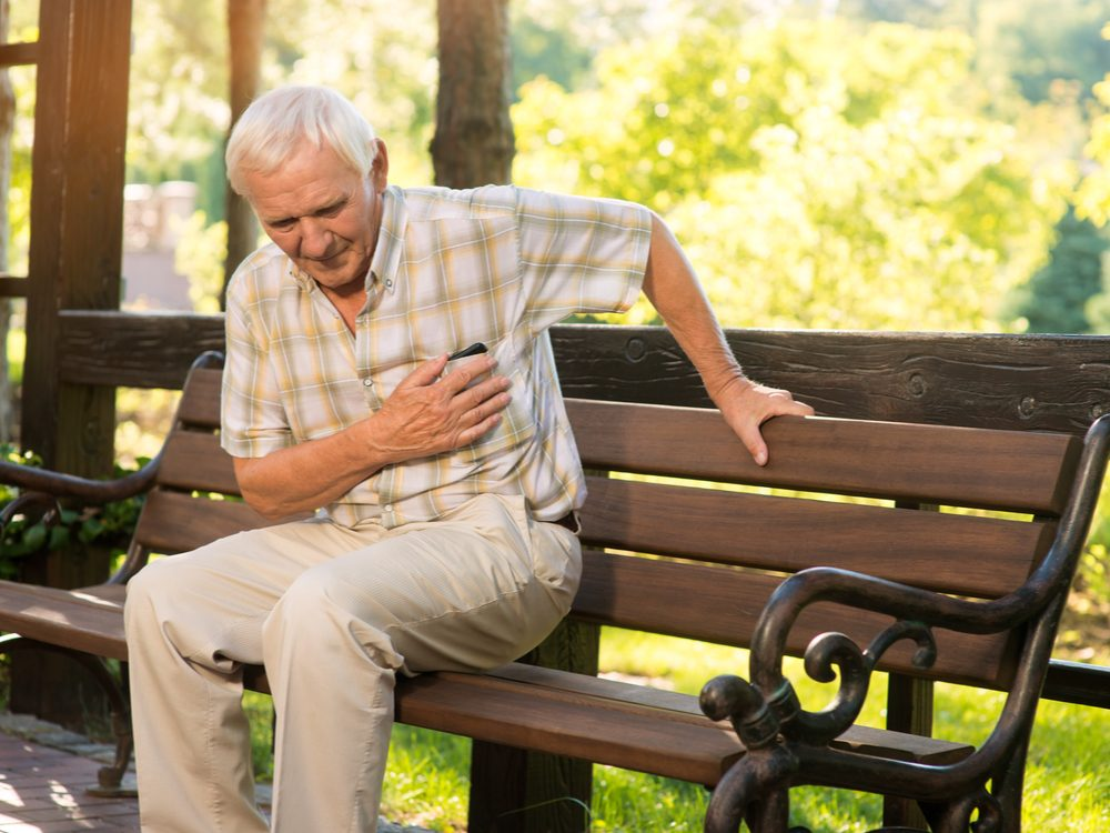Man clutching heart on bench