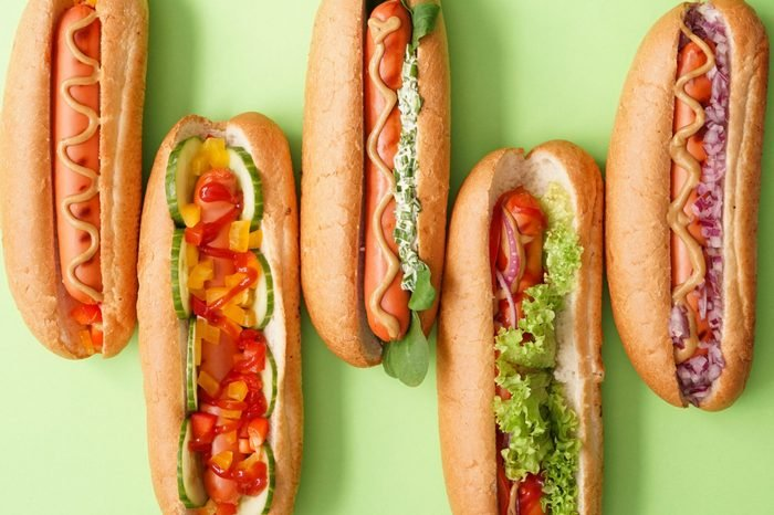 Tasty hot dogs on color background
