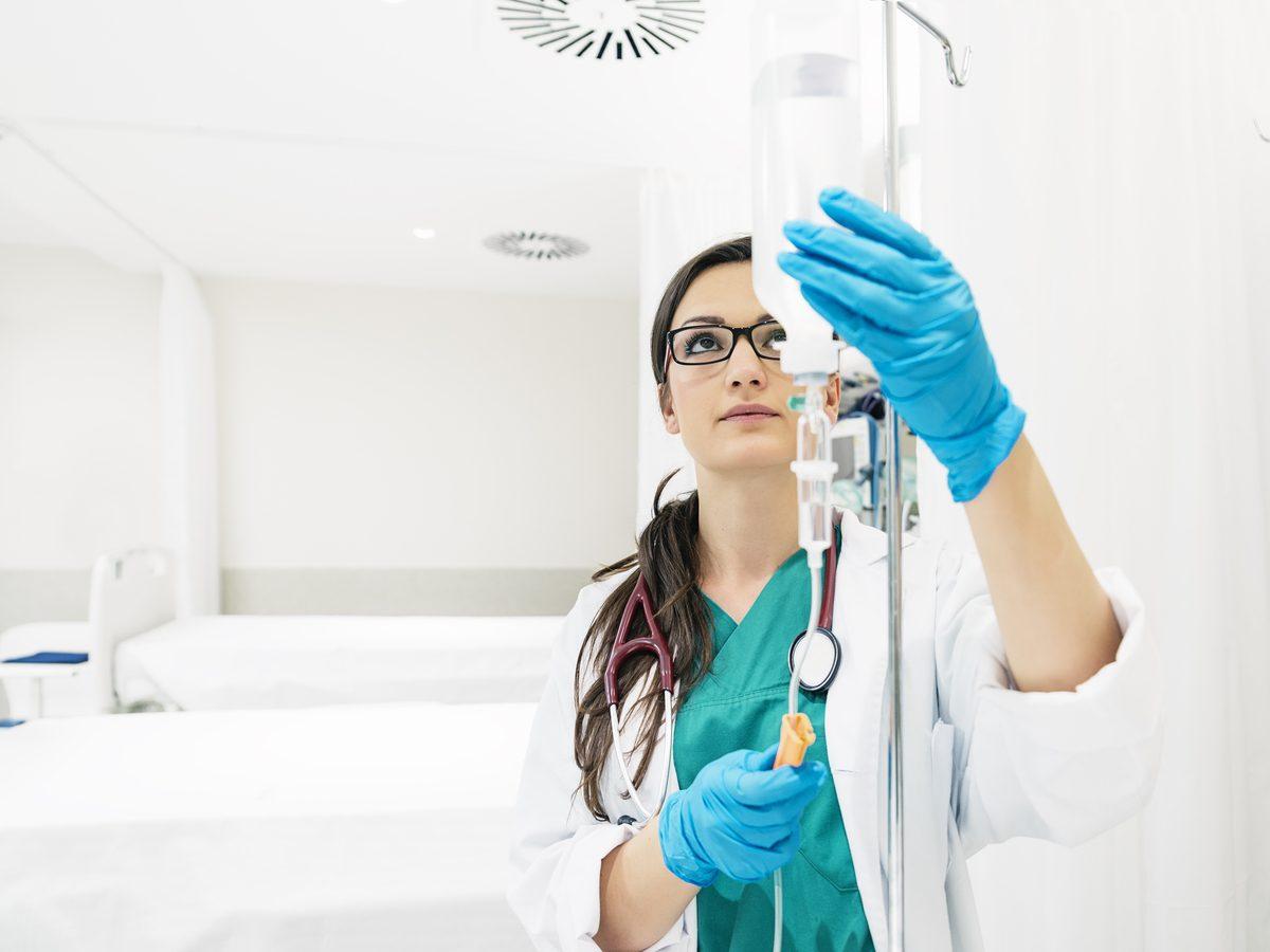 Woman examining IV in hospital