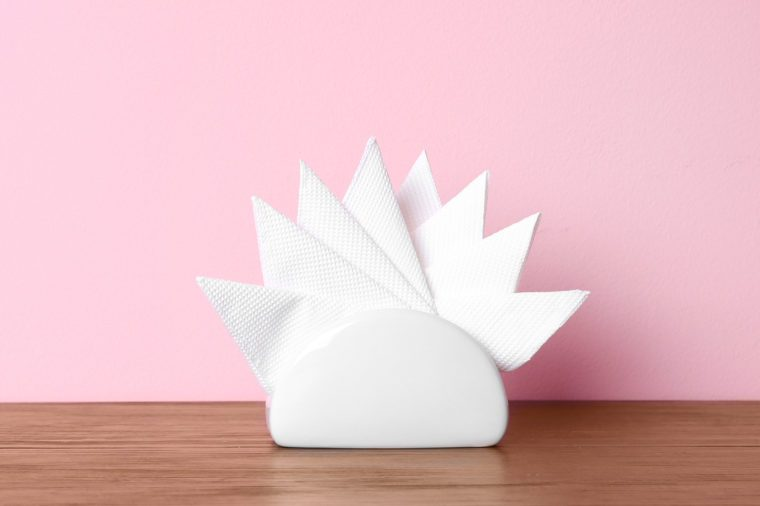 Napkin holder with paper serviettes on table against color background. Space for text