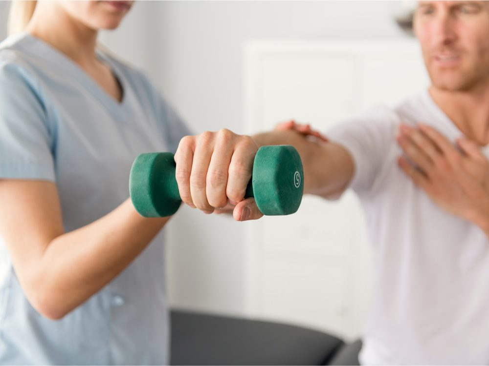 Man holding out weight during physiotherapy