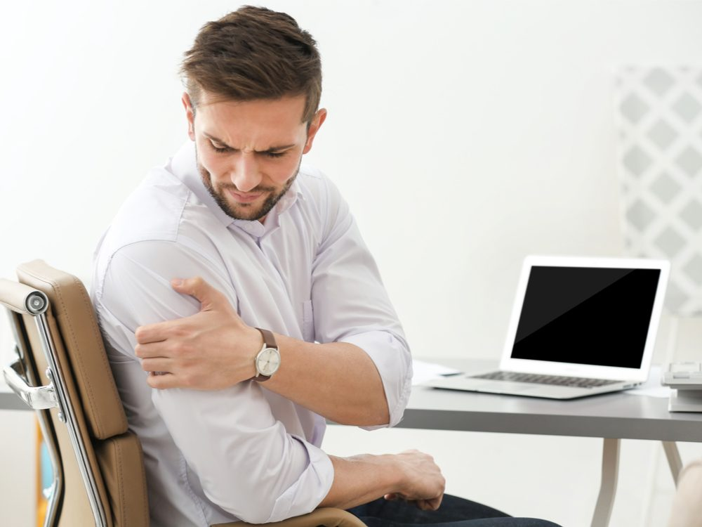 Man holding shoulder in pain at desk