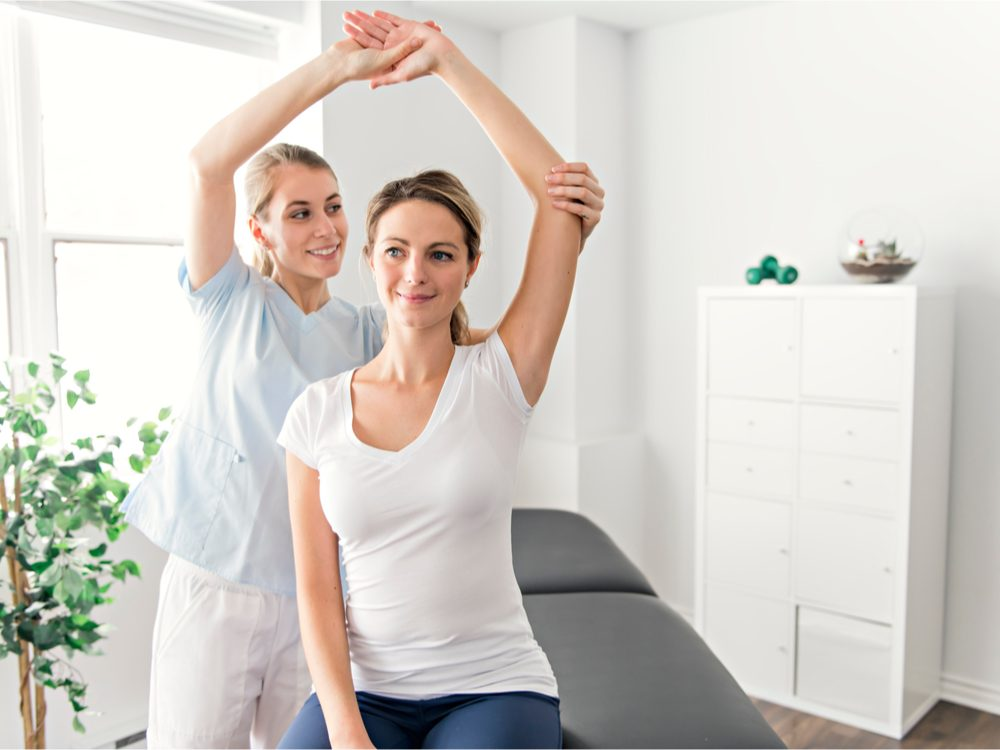 Woman raising arm during physiotherapy