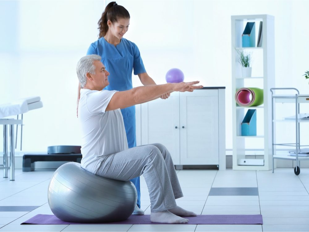 Man doing physiotherapy on exercise ball