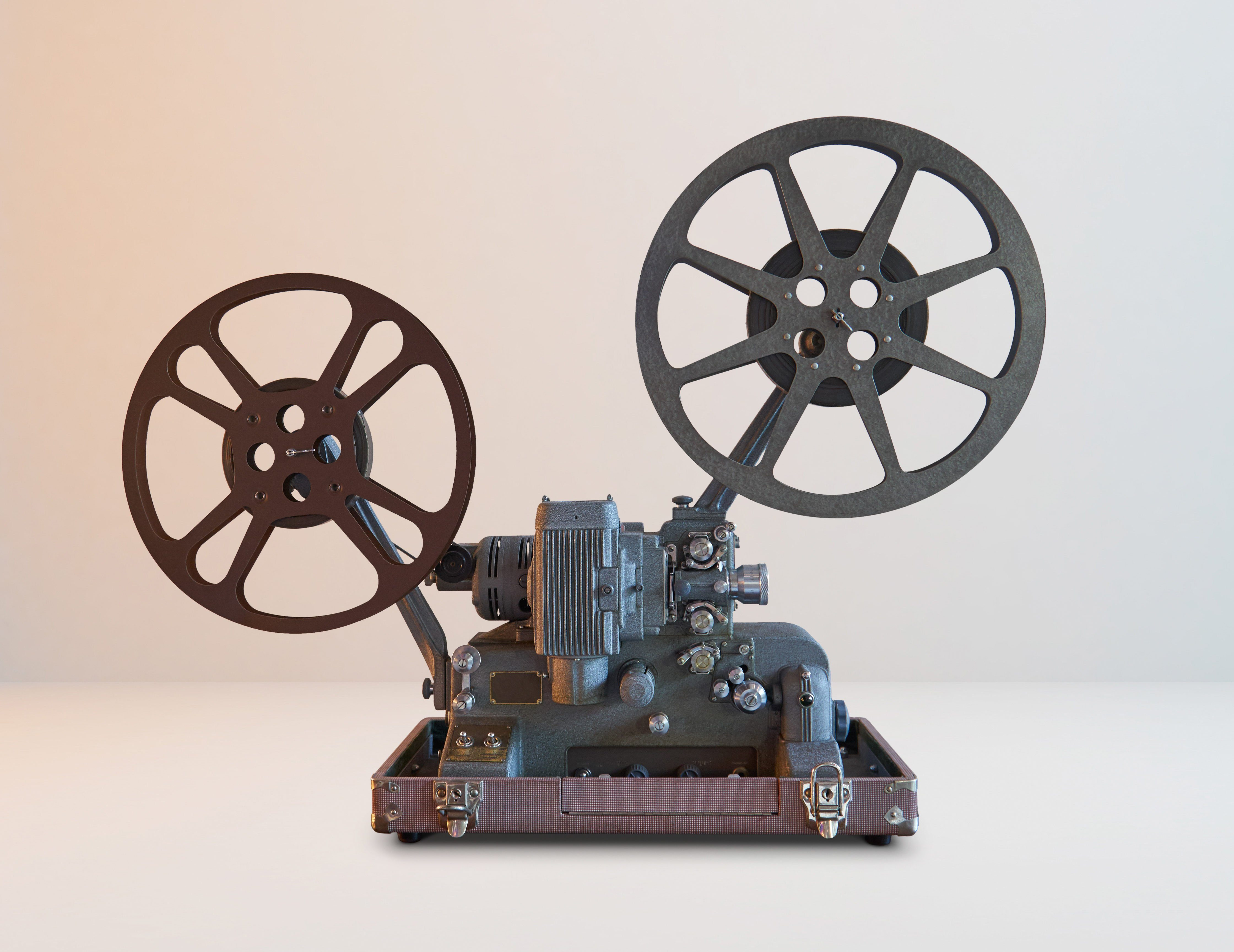 Old vintage cinema movie projector with white horizontal background .