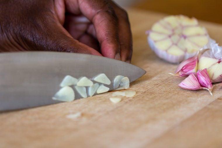 Raw garlic (Allium sativum) being chopped on a wooden chopping board