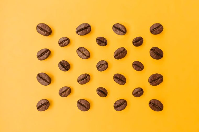 Select the best ideal coffee beans lay out on a bright orange background that emphasizes the beauty of coffee beans and perfectly blends in colors.